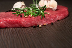 Raw beef meat on a cutting board. With a sprig of rosemary, garlic and peppercorn Stock Photo