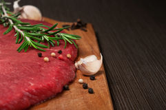 Raw beef meat on a cutting board. With a sprig of rosemary, garlic and peppercorn. Copy space. Closeup Royalty Free Stock Photo