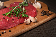 Raw beef meat on a cutting board. Top view raw beef meat on a cutting board with a sprig of rosemary, garlic and peppercorn. Copy space Royalty Free Stock Photography