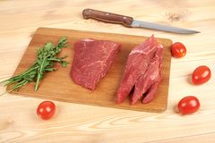Raw beef meat on cutting board with vegetables on a wooden background.  Royalty Free Stock Image