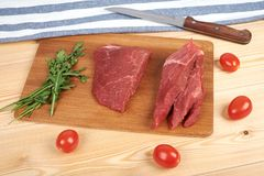 Raw beef meat on cutting board with vegetables on a wooden background.  Stock Photos