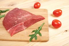Raw beef meat on cutting board with vegetables on a wooden background.  Royalty Free Stock Photo