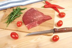 Raw beef meat on cutting board with vegetables on a wooden background.  Royalty Free Stock Images