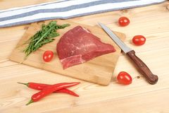 Raw beef meat on cutting board with vegetables on a wooden background.  Royalty Free Stock Photography