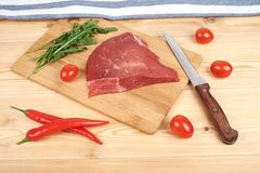 Raw beef meat on cutting board with vegetables on a wooden background.  Stock Photo