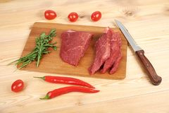 Raw beef meat on cutting board with vegetables on a wooden background.  Stock Photography