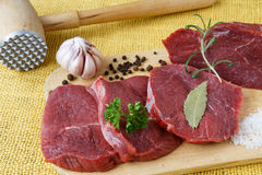 Raw beef meat on a cutting board. On yellow background Royalty Free Stock Images