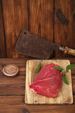 Raw beef meat fillet. On wooden  table with meat cleaver and 1lb iron weight Royalty Free Stock Images
