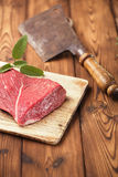 Raw beef meat fillet. On wooden  table with meat cleaver and 1lb iron weight Stock Photos
