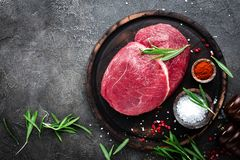 Raw beef meat. Fresh cut of beef meat on board with spices. Top view royalty free stock images
