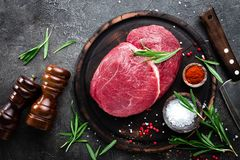 Raw beef meat. Fresh cut of beef meat on board with spices. Top view royalty free stock photos