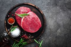 Raw beef meat. Fresh cut of beef meat on board with spices. Top view royalty free stock photo