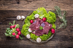 Raw beef meat with fresh vegetable. Sliced beef steak in lettuce salads radishes and mushrooms Stock Photos