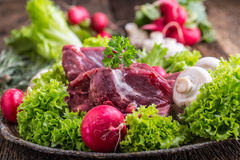 Raw beef meat with fresh vegetable. Sliced beef steak in lettuce salads radishes and mushrooms royalty free stock photo
