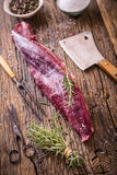 Raw beef meat. Raw beef tenderloin steak on a cutting board with rosemary pepper salt in other positions Royalty Free Stock Images