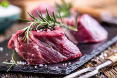 Raw beef meat. Raw beef tenderloin steak on a cutting board with rosemary pepper salt in other positions royalty free stock photo