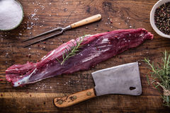 Raw beef meat. Raw beef tenderloin steak on a cutting board with rosemary pepper salt in other positions.  Stock Photo