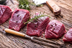 Raw beef meat. Raw beef tenderloin steak on a cutting board with rosemary pepper salt in other positions.  royalty free stock image