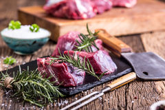 Raw beef meat. Raw beef tenderloin steak on a cutting board with rosemary pepper salt in other positions Stock Images