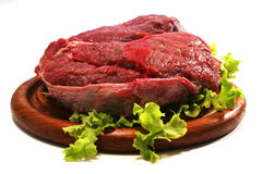 Raw beef meat and salad over white on plate Royalty Free Stock Image