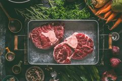 Raw beef meat shin with bone for broth, soup or stew in metal tray with ingredients for tasty cooking. Root vegetables, herbs and spices on dark rustic kitchen stock images