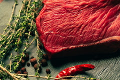 Raw beef meat with spices on slate stone kitchen board.  Royalty Free Stock Photo
