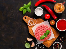 Raw beef meat steak cutlet for burger with spices and vegetables. Raw beef meat steak cutlet for burger on wooden cutting board with spices, vegetables, sauces Stock Image