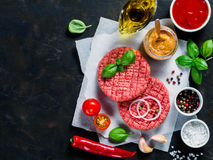 Raw beef meat steak cutlets for burger with spices and vegetables. Two raw beef meat steak cutlets for burger with spices and vegetables on black concrete Royalty Free Stock Photography