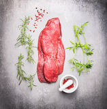 Raw beef meat steak with fresh herbs on gray stone background royalty free stock photography