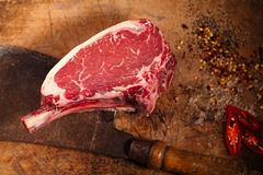 Raw beef meat steak on wooden table with meat cleaver royalty free stock photo