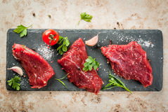 Raw beef meat tenderloin. Fresh raw beef meat tenderloin steaks on a slate cutting board on a light beige stone table. With spices salt, pepper, garlic and herbs Royalty Free Stock Images