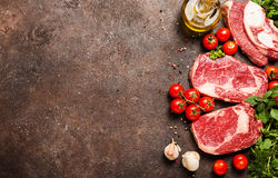 Raw beef meat and vegetables. Raw beef slices meat and vegetables on dark brown background, ingredients for healthy food, top view with copy space Stock Photography