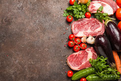 Raw beef meat and vegetables. Raw beef slices meat and vegetables on dark brown background, ingredients for healthy food, top view with copy space Royalty Free Stock Photos