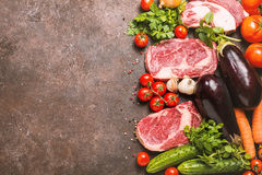Raw beef meat and vegetables. Raw beef slices meat and vegetables on dark brown background, ingredients for healthy food, top view with copy space Stock Photo