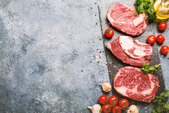 Raw beef meat and vegetables. Raw beef slices meat and vegetables on gray stone background, ingredients for healthy food, top view with copy space Stock Photos