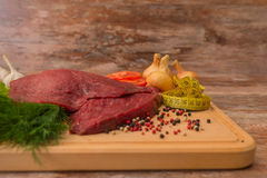 Raw beef meat with vegetables on wooden plate. Royalty Free Stock Image