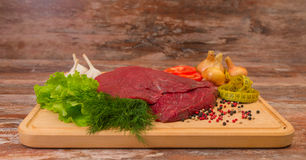 Raw beef meat with vegetables on wooden plate. Stock Image