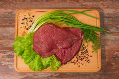 Raw beef meat with vegetables on wooden plate. Royalty Free Stock Images