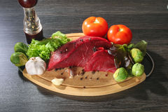 Raw beef meat with vegetables on wooden table Stock Photography