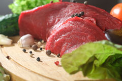 Raw beef meat with vegetables on wooden table Stock Photo