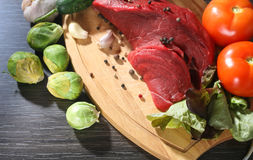 Raw beef meat with vegetables on wooden table Royalty Free Stock Photography