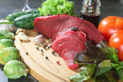 Raw beef meat with vegetables on wooden table Royalty Free Stock Photo