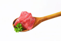Raw beef meat on wooden spoon Stock Photos