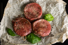 Raw beef medallions. Fresh raw beef medallions on cooking paper with basil leaves Stock Photo
