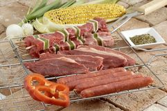 Raw Beef and Merguez. Layout of raw meat in slices and skewered, and merguez (sausage) on grilling rack with corn on cob, onions, peppers and seasonings Stock Image