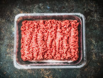 Raw beef minced meat in plastic box on rustic background, top view. Place for text Royalty Free Stock Photo