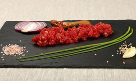 Raw beef minced meat and spices on black board. Raw minced beef red meat cutlet, spices, peppercorn in wooden scoop, spring green chive, onion, garlic cloves and Royalty Free Stock Images