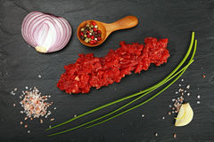 Raw beef minced meat and spices on black board. Raw minced beef red meat cutlet, spices, peppercorns, spring shallot onions, garlic and salt on black slate board Stock Photo