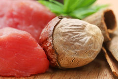 Raw beef with nutmeg other spices. On wooden surface Royalty Free Stock Images