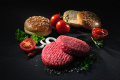 Raw beef patties with other ingredients for hamburgers Stock Image